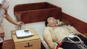 Doutor do cardiologista que prepara o paciente para a remoção do cardiograma filme