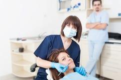 Doutor do dentista da mulher com o assistente paciente e masculino imagem de stock royalty free