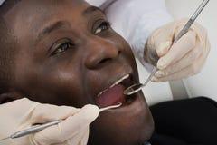 Doutor Doing Dental Check acima do paciente foto de stock royalty free