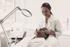 Doutor Doing Dermatology Procedure na clínica fotografia de stock