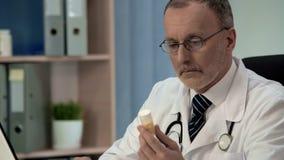 Doutor duvidoso que olha comprimidos, medicinas de má qualidade falsas, placebo foto de stock