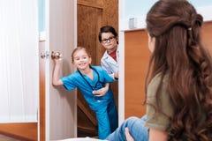 Doutor e enfermeira pequenos de vista pacientes da menina no hospital Foto de Stock Royalty Free