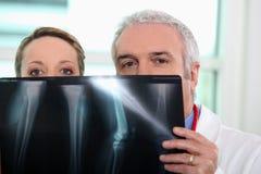 Doutor e enfermeira que olham o raio X Fotos de Stock Royalty Free