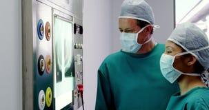 Doutor e enfermeira que olham o raio X vídeos de arquivo