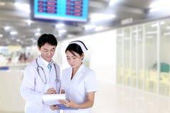 doutor e enfermeira que reveem a carta médica fotografia de stock royalty free