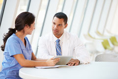 Doutor e enfermeira que têm a reunião informal na cantina do hospital fotografia de stock