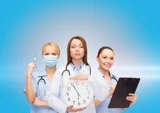 Doutor e enfermeiras fêmeas calmos com pulso de disparo de parede Fotografia de Stock Royalty Free
