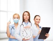Doutor e enfermeiras fêmeas calmos com pulso de disparo de parede Fotografia de Stock