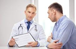 Doutor e paciente com cardiograma na prancheta imagem de stock royalty free