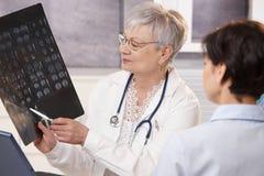 Doutor e paciente que discutem resultados do raio X. fotografia de stock royalty free