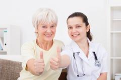 Doutor e polegar mostrando paciente acima Imagem de Stock