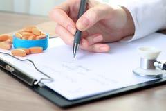 Doutor em um labcoat branco que escreve para fora a prescrição de RX Foto de Stock Royalty Free