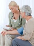 Doutor encantador que toma a pressão sanguínea Imagem de Stock Royalty Free