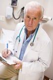 Doutor envelhecido médio Escrita Seu Prancheta Fotos de Stock