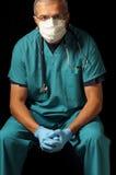 Doutor envelhecido médio assentado sobre o preto Fotos de Stock Royalty Free