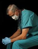 Doutor envelhecido médio assentado sobre o preto Foto de Stock