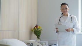 Doutor fêmea alegre que está em uma divisão de hospital video estoque