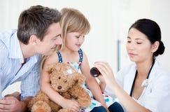 Doutor fêmea asiático que dá o xarope a uma menina Foto de Stock Royalty Free
