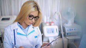 Doutor fêmea atrativo que sorri em uma sala de hospital video estoque