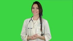Doutor fêmea bonito com estetoscópio que sorri na câmera em uma tela verde, chave do croma filme