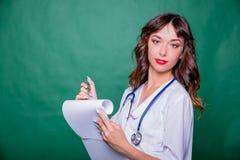 Doutor fêmea bonito que guardara o sorriso da prancheta Doutor que escreve em uma prancheta, escritório médico, clínica, trabalho foto de stock royalty free