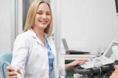 Doutor fêmea bonito que levanta ao fazer a ecografia fotos de stock royalty free