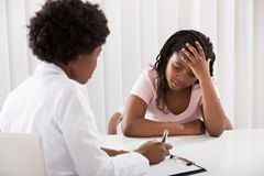 Doutor fêmea Comforting Depressed Patient fotografia de stock royalty free