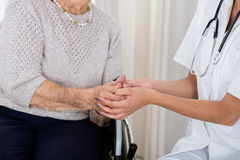 Doutor fêmea Consoling Senior Patient fotos de stock royalty free