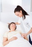 Doutor fêmea Consoling Senior Woman Foto de Stock