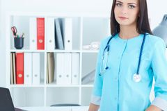 Doutor fêmea de sorriso bonito da medicina que está em seu escritório que olha in camera Conceito da recepção do médico imagens de stock