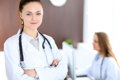 Doutor fêmea de sorriso dos jovens bonitos que está em um hospital com seu colega no fundo imagens de stock royalty free