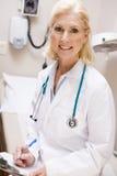 Doutor fêmea envelhecido médio Escrita Um Prancheta Foto de Stock Royalty Free