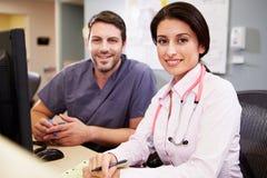 Doutor fêmea With Male Nurse que trabalha na estação das enfermeiras foto de stock