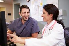 Doutor fêmea With Male Nurse que trabalha na estação das enfermeiras foto de stock royalty free