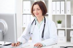 Doutor fêmea moreno novo que senta-se em uma mesa e que trabalha no computador no escritório do hospital Imagem de Stock