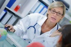 Doutor fêmea na conversação com o paciente no escritório médico imagens de stock
