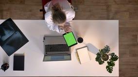 Doutor fêmea novo no revestimento branco usando a tabuleta com chromakey, topshot, sentando-se na tabela com portátil, conceito m video estoque