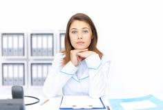 Doutor fêmea novo que senta-se na mesa no hospital Fotografia de Stock