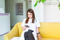 Doutor fêmea novo que senta-se no sofá amarelo no centro médico com telefone celular e café bebendo durante sua ruptura Estudante imagem de stock royalty free