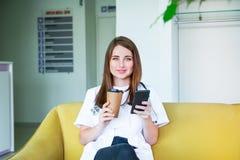 Doutor fêmea novo que senta-se no sofá amarelo no centro médico com telefone celular e café bebendo durante sua ruptura Estudante foto de stock royalty free