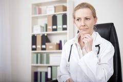 Doutor fêmea pensativo com mão em seu Chin Foto de Stock Royalty Free
