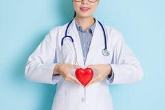 Doutor fêmea profissional de sorriso que guarda o coração fotos de stock