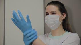 Doutor fêmea profissional seguro na máscara e no tampão na sala de hospital que calça luvas médicas azuis Médico da mulher em vídeos de arquivo