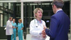 Doutor fêmea que agita as mãos com o homem de negócios no corredor