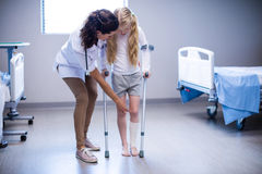 Doutor fêmea que ajuda à menina a andar com as muletas na divisão imagem de stock