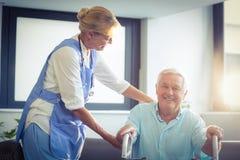 Doutor fêmea que ajuda o homem superior a andar com caminhante imagem de stock royalty free