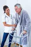 Doutor fêmea que ajuda o homem superior a andar com caminhante foto de stock royalty free