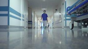 Doutor fêmea que anda através do corredor longo video estoque