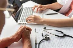 Doutor fêmea que consulta com o paciente do homem superior foto de stock royalty free