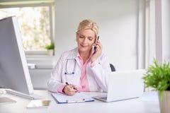 Doutor fêmea que consulta com seu paciente no telefone celular fotos de stock royalty free